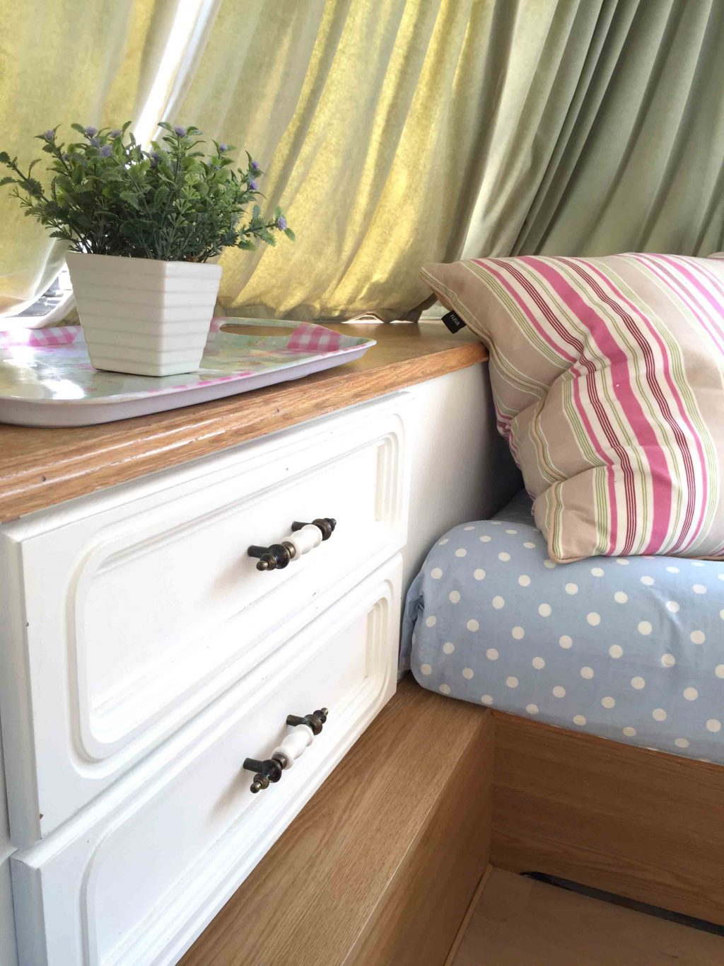 Close up of the drawer unit and shelf in Dolly the caravan; after it had been painted as part of my first caravan makeover. I kept the original green velvet curtains but covered the seats with blue polkadot fabric. More info on both of my caravan makeovers on the blog!