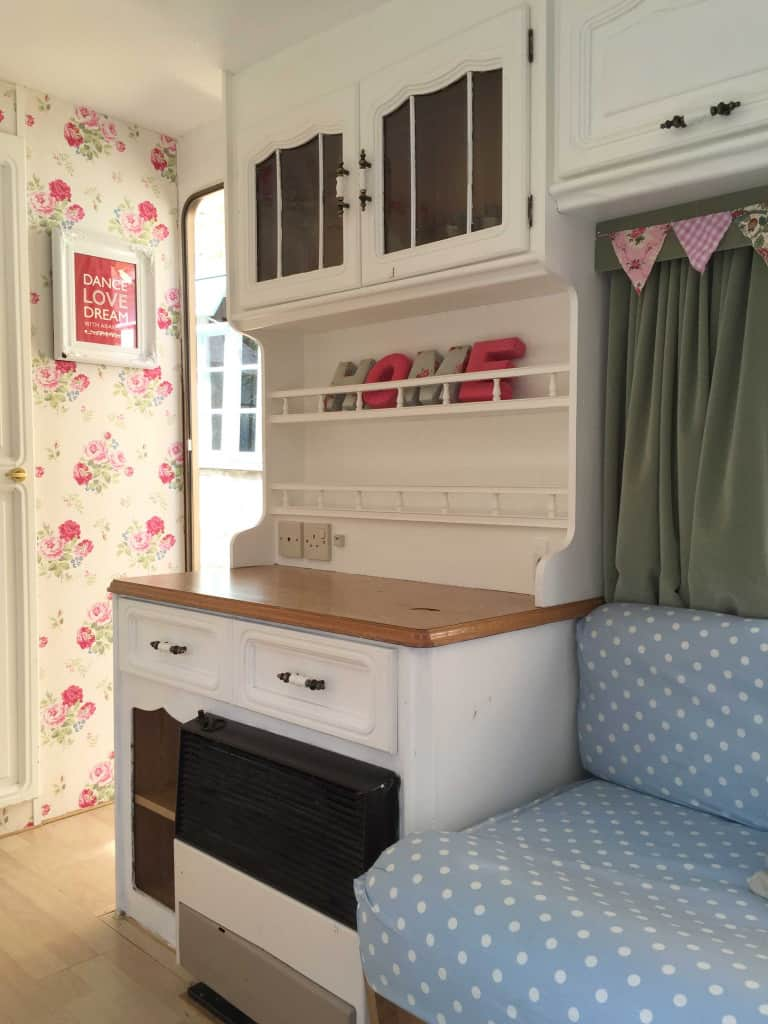 Looking towards the doorway of Dolly the caravan! I painted the cupboard area in fresh white and wallpapered the walls as part of my caravan makeover. More info on both of my caravan makeovers on the blog!