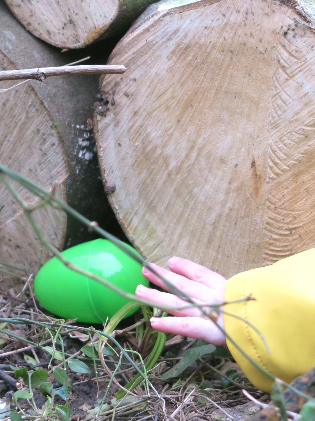 A little hand reaching for a colourful egg at an Easter egg hunt