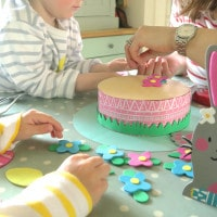 Family making Easter bonnets at the kitchen table