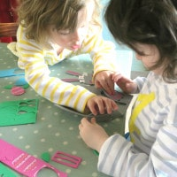 Twins making Easter bonnets at the kitchen table