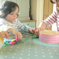 Mum and toddler making Easter bonnets at the kitchen table