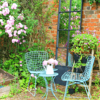 The roses in our walled garden really come into their own during the summer. This sunny spot is decorated with a garden mirror plus an outside seating area to enjoy the view.