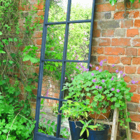 A strategically placed garden mirror will illuminate even the gloomiest corner and also give tantalising glimpses into other areas. This window pane mirror offers lots of different views.
