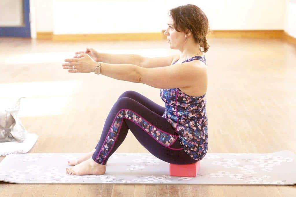 Pilates bow and arrow — Step 1 — Sit up tall on your sit bones — a block is a useful tool to help you sit up nice and straight.