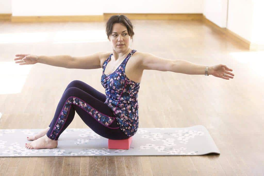 Pilates Bow and arrow — Step 3 — Continue bringing your arm back and rotating your spine — with your hips facing forwards — until you reach your limit. Don't try to twist round any further than is comfortable and don't strain your neck.