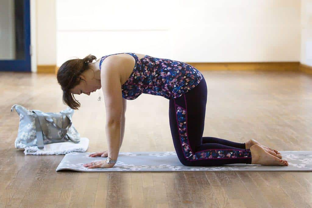 Pilates cat stretch — Starting with your tailbone, start to tip your pelvis forward.  Pull your navel in towards your spine and squeeze your bottom to try to create a rounded C shape with your lower back.