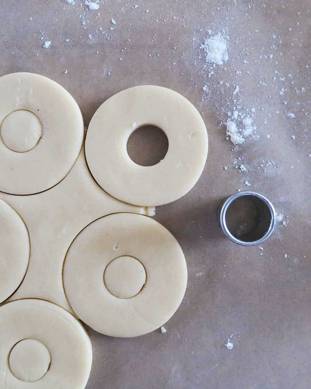 Shortbread cookie dough, cut into rounds, waiting to be turned into edible flower biscuits