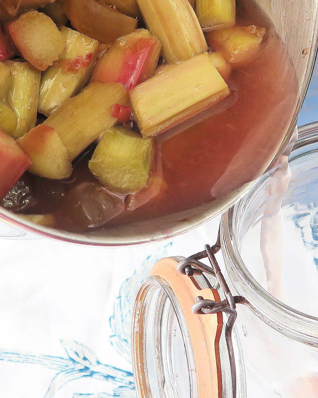pouring homemade ginger and rhubarb gin into a jar