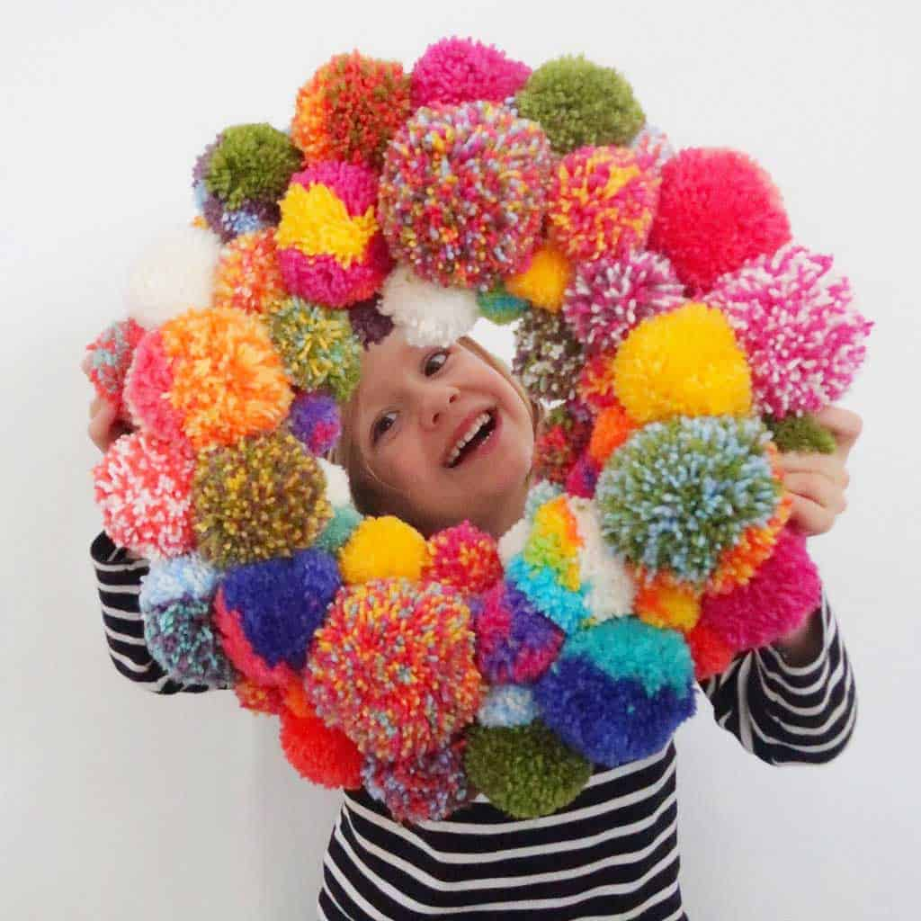 Want to Make a Pom Pom Wreath? This is such a fun project and it looks just like the Anthropologie version.