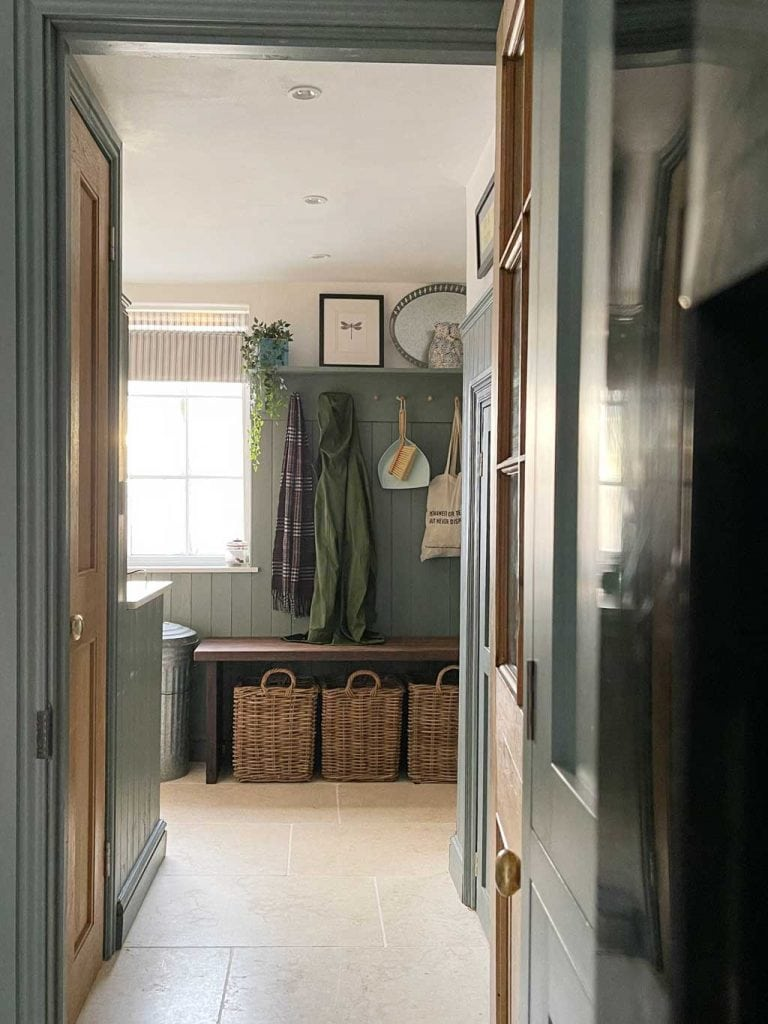 Green painted tongue and groove woodwork in the boot room of The Listed Home — with Monte Carlo limestone floor from Quorn Stone