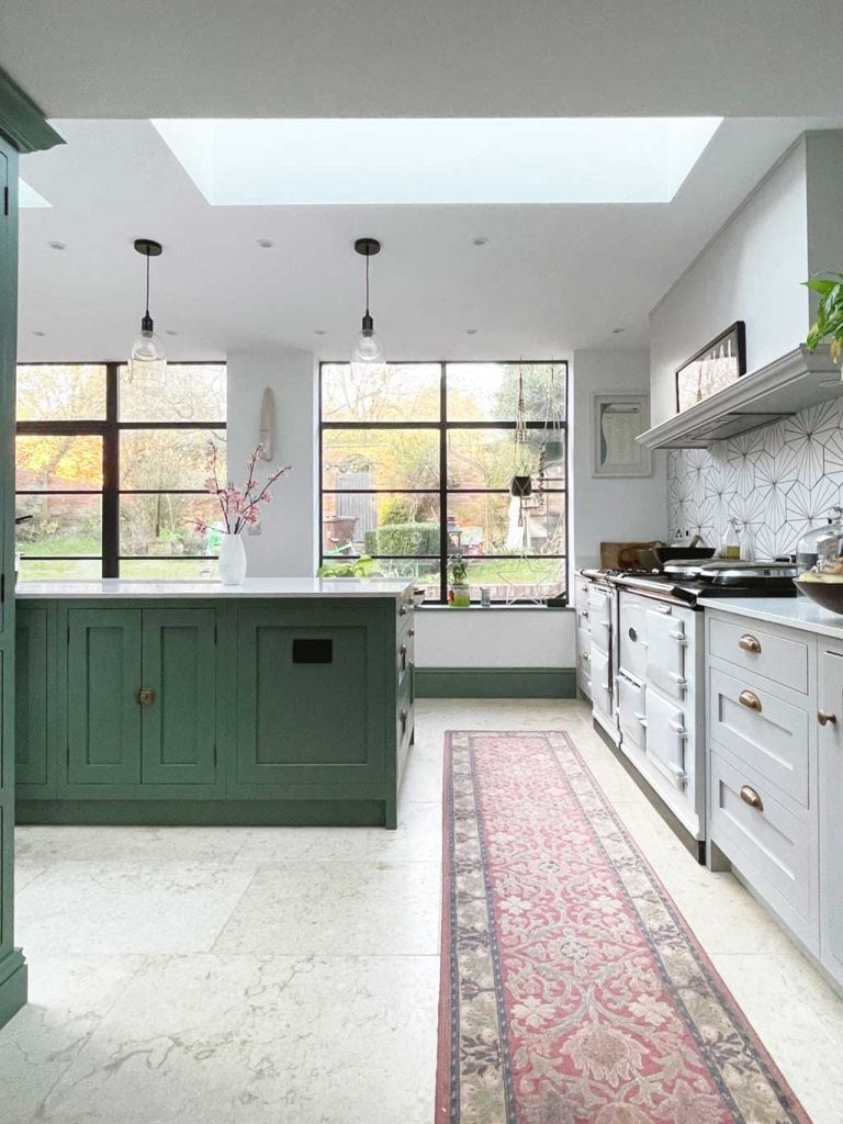 Green and grey shaker kitchen in The Listed Home — with Crittall windows and doors. And Monte Carlo limestone floor from Quorn Stone